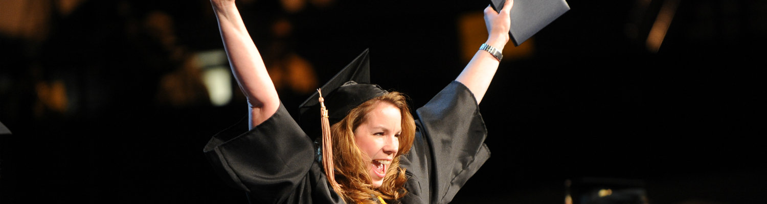 A graduate of Kent State is all smiles during her commencement ceremony.